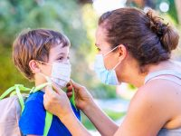 Caucasian Mature woman and son face to face she is putting him on a protective face mask before he goes back to school